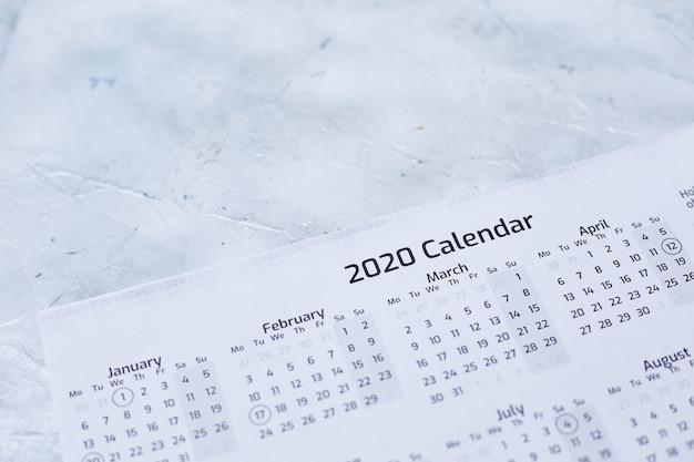 Primer plano de un calendario 2020 sobre una superficie con textura blanca