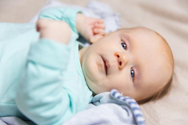 Primer plano de calma dulce bebé acostado en la cama cubierta