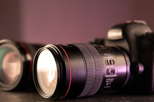 Primer plano de cámara digital profesional sobre un fondo borroso. el concepto de tecnología para trabajar con fotos y videos.