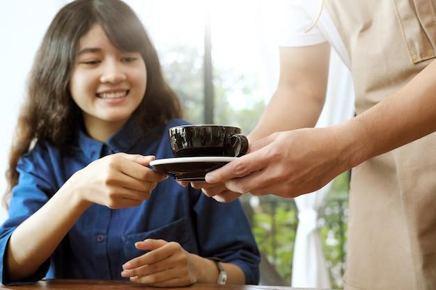 Primer plano de una camarera que sirve una taza de café al cliente hermoso joven.