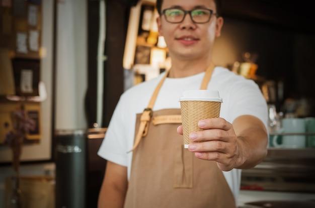 Primer plano de una camarera sirviendo una taza de café. enfoque selectivo