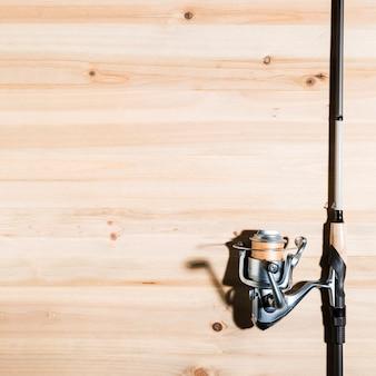 Primer plano de la caña de pescar en el escritorio de madera