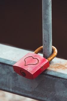 Primer plano de un candado de metal con un corazón colgando de una valla