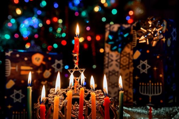 Primer plano de un candelabro de januca ardiendo con velas menorah