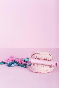 Primer plano de cápsulas y píldoras además de dientes molde con jeringa