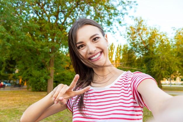 Primer plano de la cara de la chica de moda está haciendo selfie foto