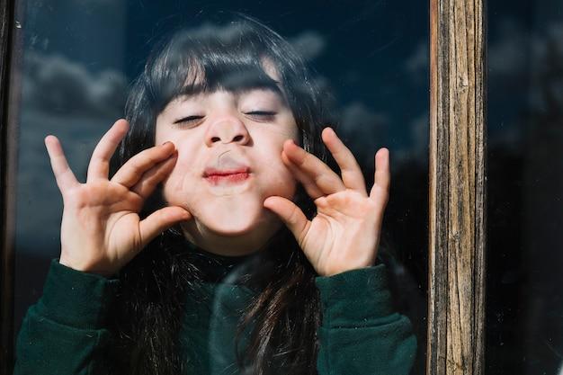 Primer plano de la cara de una niña a través de la ventana de cristal