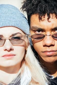 Primer plano de la cara de la pareja interracial con elegantes gafas de sol mirando a la cámara