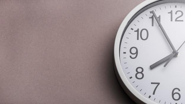 Primer plano de la cara del reloj contra el fondo gris