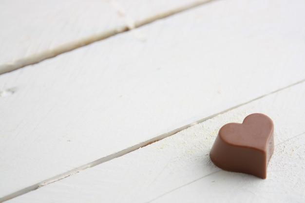 Primer plano de un caramelo de chocolate en forma de corazón sobre una mesa de madera blanca