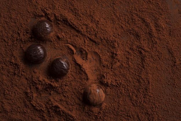 Primer plano de caramelos de chocolate sobre chocolate en polvo
