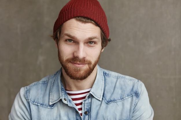 Primer plano de carismático hombre joven europeo de moda con barba espesa con sombrero de moda