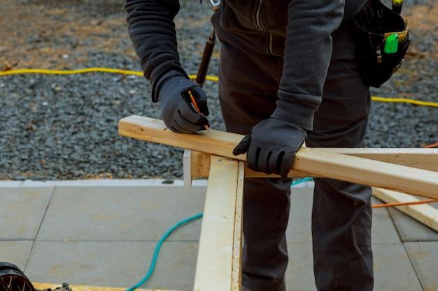 Primer plano de un carpintero constructor de manos en el trabajo con construcción de madera