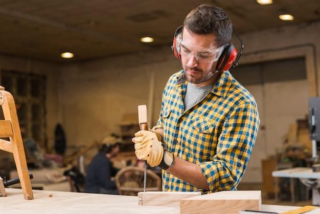 Primer plano de un carpintero golpeando martillo en cincel en el bloque de madera en el taller