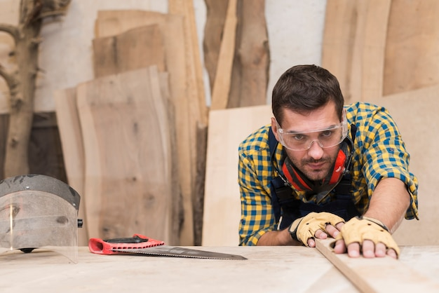 Primer plano de un carpintero hombre trabajando en el taller