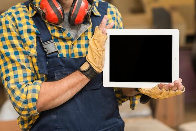 Primer plano de un carpintero macho mostrando tableta digital en su mano