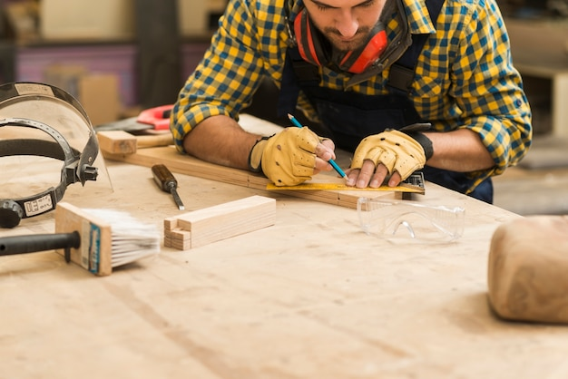 Primer plano de un carpintero masculino que mide el bloque de madera con la regla y el lápiz en el banco de trabajo de madera