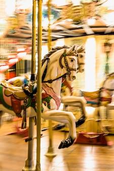 Primer plano de un carrusel de caballos iluminado detalle