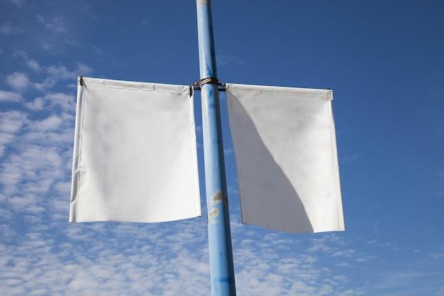 Primer plano del cartel de la bandera del poste de la lámpara blanca contra el cielo azul