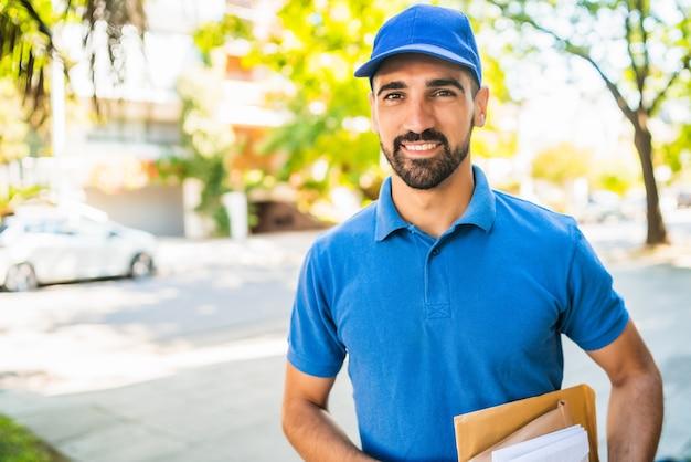 Primer plano de un cartero llevando paquetes y cartas al aire libre en la calle. concepto de servicio postal de entrega.