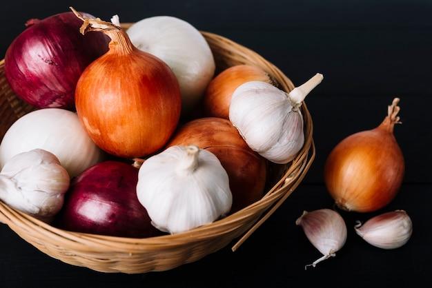 Primer plano de cebollas frescas y bulbos de ajo en la cesta sobre fondo negro