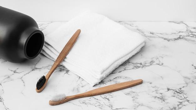 Primer plano de cepillo de dientes de madera; toallas blancas y tarro sobre tablero de mesa de mármol.