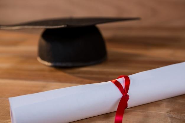 Primer plano de certificado de graduación con la tarjeta del mortero sobre una mesa