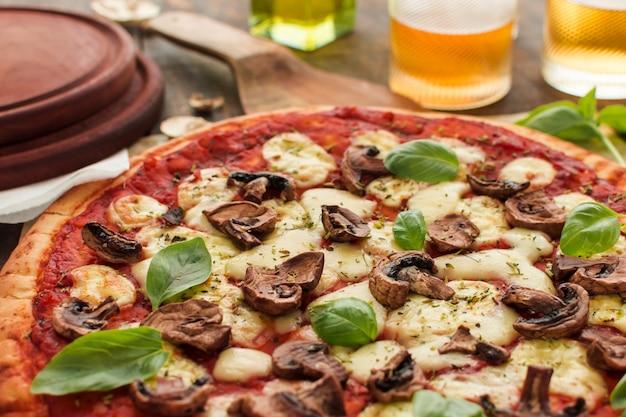 Primer plano de champiñones y aderezo de albahaca en pan de pizza con queso derretido