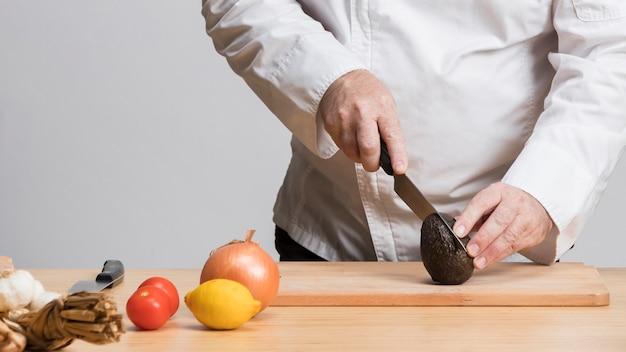 Primer plano chef cortar aguacate