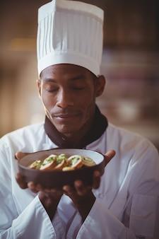 Primer plano del chef con los ojos cerrados oliendo comida