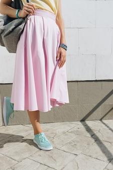 Primer plano de una chica en falda rosa, camisa amarilla y con una mochila de pie contra una pared blanca