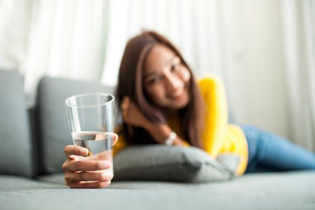 Primer plano de chica feliz con un vaso de agua