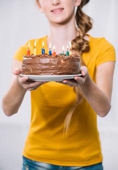 Primer plano de una chica con pastel de cumpleaños en un plato blanco sobre fondo blanco