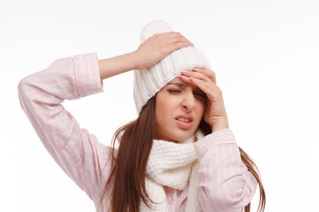 Primer plano de chica en pijamas con dolor de cabeza