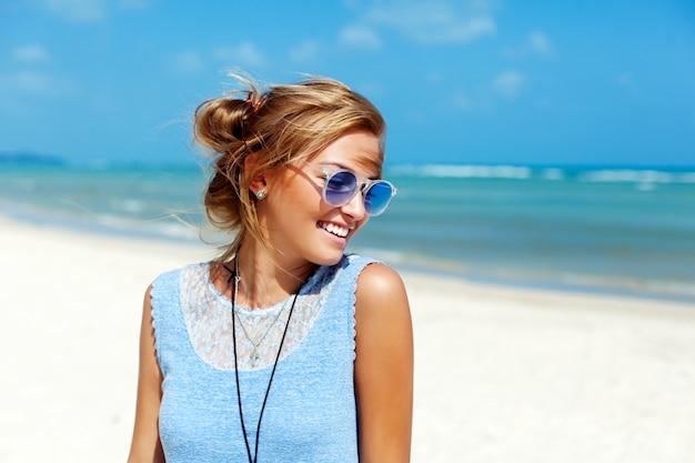 Primer plano de chica rubia con gafas de sol disfrutando de su tiempo