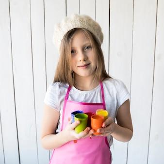 Primer plano de la chica rubia que llevaba gorra en la cabeza con varias botellas de pintura de colores en la mano