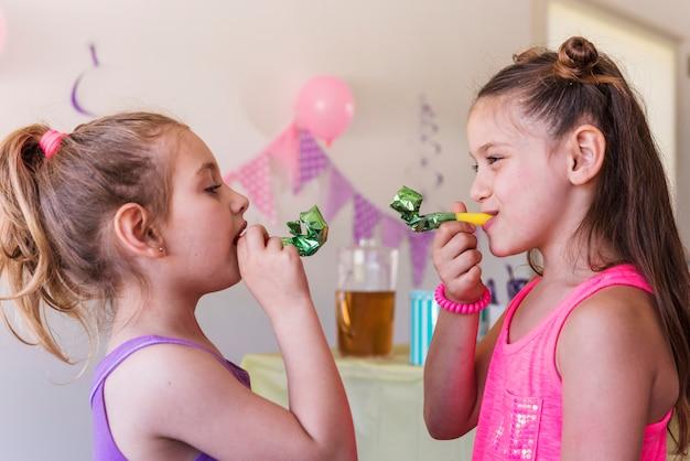 Primer plano de chicas lindas soplando cuerno fiesta disfrutando en fiesta