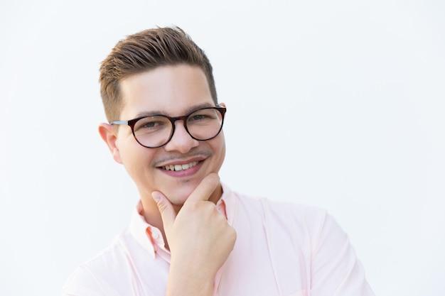 Primer plano de un chico alegre en gafas tocando la barbilla