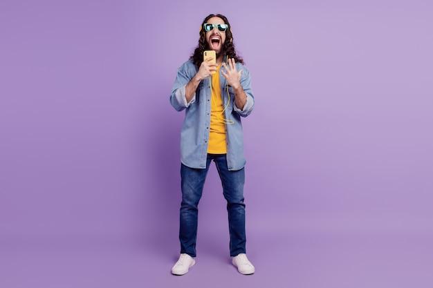 Primer plano de un chico feliz mantenga el teléfono celular use auriculares de gafas de sol cantan la canción