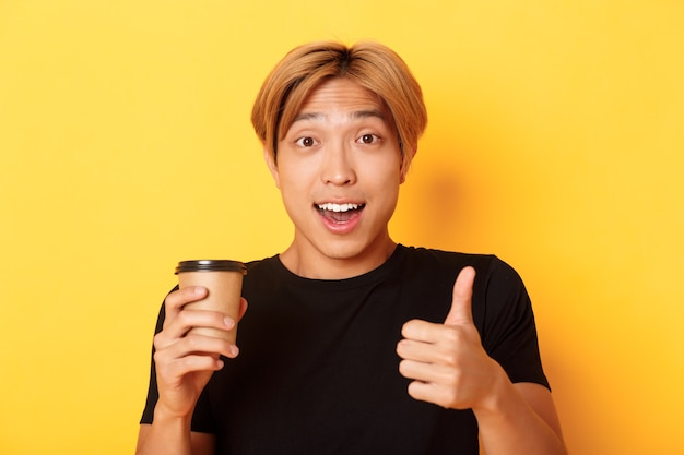 Primer plano de chico guapo asiático sorprendido recomendar café, sosteniendo una taza de café y mostrando el pulgar hacia arriba en señal de aprobación, sonriendo complacido sobre la pared amarilla.