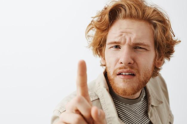 Primer plano de chico pelirrojo barbudo confundido posando contra la pared blanca