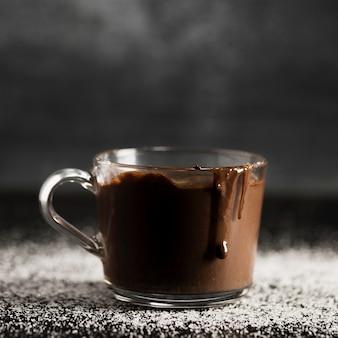 Primer plano de chocolate derretido en una taza transparente