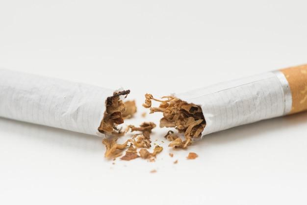 Primer plano de cigarrillos y tabaco sobre fondo blanco