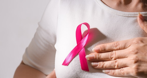 Primer plano de una cinta insignia rosa en el pecho de la mujer para apoyar la causa del cáncer de mama