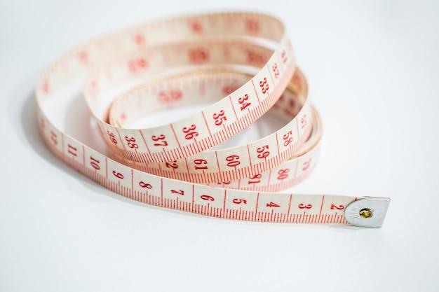 Primer plano de una cinta métrica blanca y roja sobre la mesa bajo las luces - concepto de diseño
