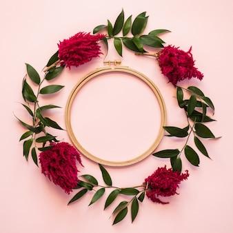 Primer plano de un círculo de flores frescas y hojas verdes sobre un fondo rosa - copiar espacio