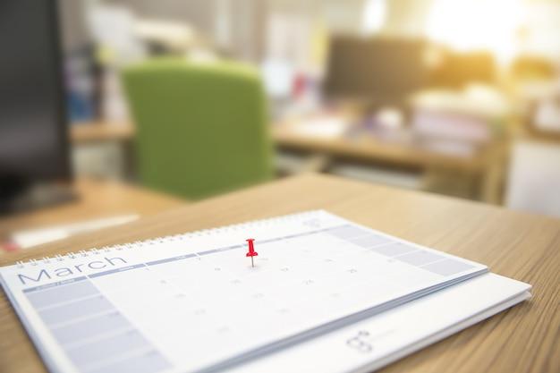 Primer plano de una clavija roja en el calendario de escritorio en blanco.