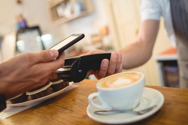Primer plano del cliente con celular y barista con lector de tarjetas