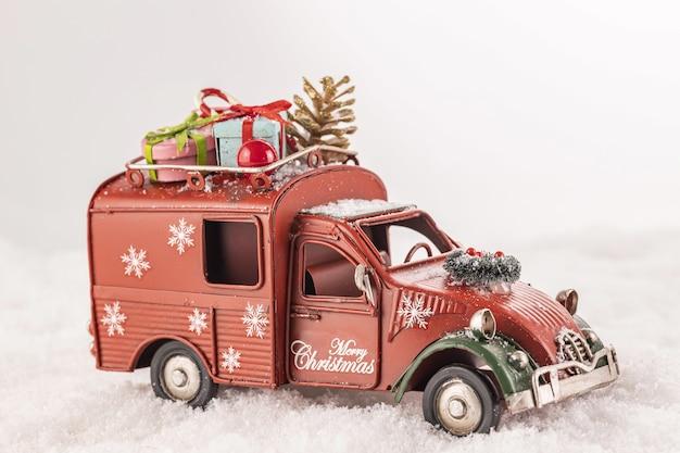 Primer plano de un coche de juguete con adornos navideños sobre nieve artificial sobre un fondo blanco.