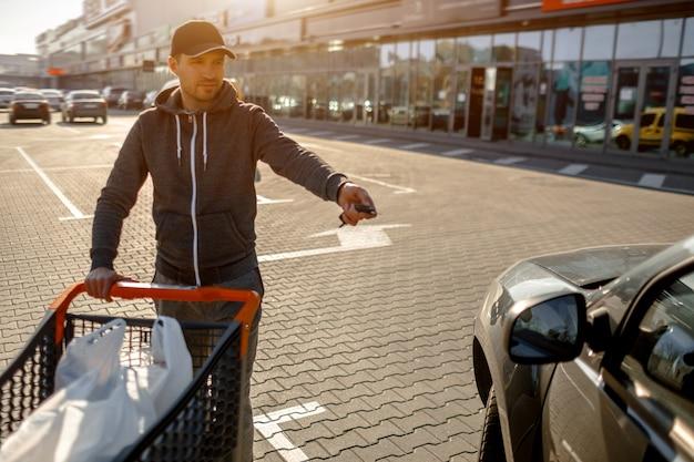 Primer plano de un cochecito con comida cerca de un gran supermercado en un centro comercial suburbano. un hombre está parado cerca de un automóvil en un estacionamiento después de una compra exitosa.